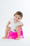 Piccola ragazza sorridente che si siede su un vaso Isolato su priorità bassa bianca Immagini Stock Libere da Diritti