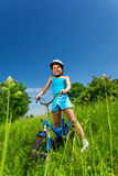 Piccola ragazza sorridente che si siede su una bicicletta Fotografia Stock Libera da Diritti