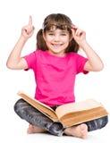 Piccola ragazza sorridente dello studente in occhiali con il libro ed il dito su isolayed su bianco Immagini Stock Libere da Diritti