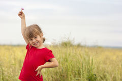 Piccola ragazza sorridente sveglia che giudica poco fiore su disponibile Fotografia Stock Libera da Diritti