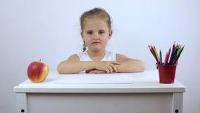 Piccola ragazza stanca e frustrata che si siede ad uno scrittorio della scuola archivi video