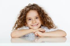 Piccola ragazza sveglia adorabile con capelli ricci in blusa bianca, messa ad una tavola, esaminante macchina fotografica, sopra  fotografia stock