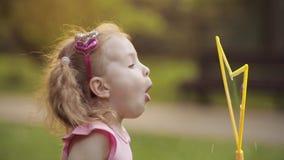 Piccola ragazza sveglia allegra sicura che soffia il primo piano enorme di medium del ventilatore della bolla di sapone dell'aria stock footage