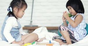 Piccola ragazza sveglia asiatica due che gioca insieme blocco di legno colourful sul letto video d archivio