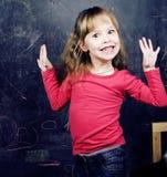 Piccola ragazza sveglia in aula a scrittura della lavagna Immagine Stock Libera da Diritti