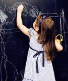 Piccola ragazza sveglia in aula a scrittura della lavagna che sorride, bambino in età prescolare da solo posteriore, concetto del Fotografia Stock