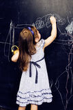 Piccola ragazza sveglia in aula a scrittura della lavagna che sorride, bambino in età prescolare da solo posteriore, concetto del Immagini Stock Libere da Diritti