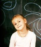 Piccola ragazza sveglia in aula a scrittura della lavagna che sorride, bambino in età prescolare da solo posteriore, concetto del Fotografie Stock Libere da Diritti