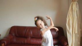 Piccola ragazza sveglia che balla e che imbroglia intorno a casa archivi video