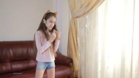 Piccola ragazza sveglia che balla e che imbroglia intorno a casa stock footage