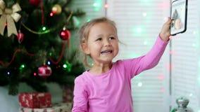 Piccola ragazza sveglia che fa selfie con l'albero di Natale sui precedenti archivi video