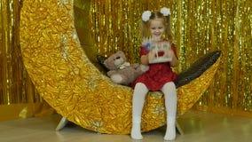 Piccola ragazza sveglia che gioca con il suo orsacchiotto bambino in una stanza dei giochi I bambini alimentano le bambole ed il  video d archivio