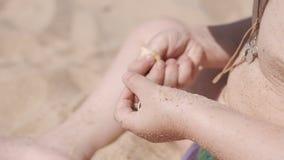 Piccola ragazza sveglia che gioca con la sabbia e le conchiglie sulla spiaggia Chiuda su in 4K stock footage