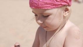 Piccola ragazza sveglia che gioca con la sabbia e le conchiglie sulla spiaggia Chiuda su in UHD archivi video