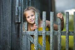 Piccola ragazza sveglia che guarda da dietro un recinto di legno felice Immagini Stock