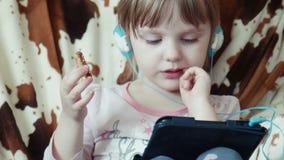 Piccola ragazza sveglia che per mezzo della compressa digitale archivi video