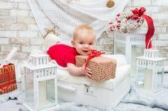 Piccola ragazza sveglia cinque mesi la vigilia del Natale con un regalo Immagini Stock Libere da Diritti