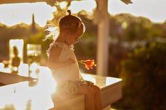 Piccola ragazza sveglia con il fiore in sua mano che si siede sulla tavola Fotografia Stock Libera da Diritti