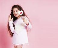 Piccola ragazza sveglia con la caramella sulla posa rosa emozionale, concetto del fondo della gente di stile di vita Immagine Stock