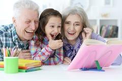 Piccola ragazza sveglia con lo studio dei nonni Immagine Stock Libera da Diritti