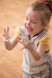 Piccola ragazza sveglia coperta di risata della farina Immagini Stock Libere da Diritti