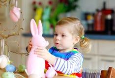 Piccola ragazza sveglia del bambino che decora albero e coniglietto con le uova di plastica pastelli colorate Bambino felice del  fotografia stock