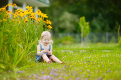 Piccola ragazza sveglia del bambino che si siede sull'erba Immagine Stock