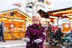 Piccola ragazza sveglia del bambino divertendosi sul mercato tradizionale di Natale durante le forti precipitazioni nevose Godere fotografia stock