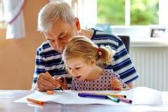 Piccola ragazza sveglia del bambino del bambino e pittura di prima generazione senior bella con le matite variopinte a casa Nipot fotografie stock