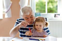 Piccola ragazza sveglia del bambino del bambino e pittura di prima generazione senior bella con le matite variopinte a casa Nipot immagini stock