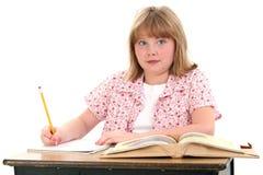 Piccola ragazza sveglia del banco che si siede in scrittorio con i libri Immagini Stock