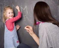 Piccola ragazza sveglia dell'allievo con l'insegnante nella scrittura dell'aula sulla lavagna Immagine Stock