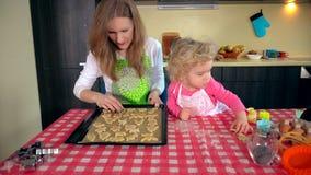 Piccola ragazza sveglia dell'assistente con i bei biscotti del posto della madre nella latta del forno stock footage