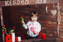 Piccola ragazza sveglia felice con i fiori in mani a casa Fotografie Stock Libere da Diritti