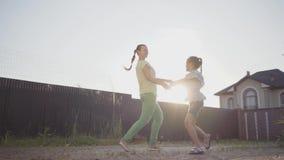 Piccola ragazza sveglia felice e sua la madre che filano intorno tenersi per mano nel cortile La donna ed il bambino divertendosi archivi video
