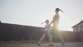 Piccola ragazza sveglia felice e sua la madre che filano intorno tenersi per mano nel cortile La donna ed il bambino divertendosi stock footage