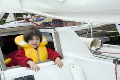 Piccola ragazza sveglia in giubbotto di salvataggio sull'yacht immagini stock libere da diritti