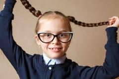 Piccola ragazza sveglia nei vetri che tirano i suoi capelli Fotografia Stock