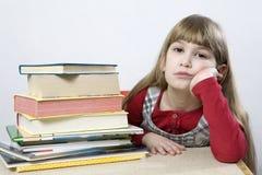 Piccola ragazza triste sveglia con un mucchio di seduta del libro Fotografia Stock