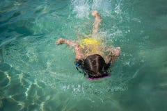 Piccola ragazza in una nuotata della maschera di nuoto in acqua pulita del turchese Fotografia Stock