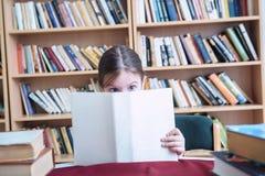 Piccola ragazza in vecchio libro di lettura delle biblioteche Immagine Stock Libera da Diritti