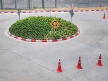 Piccola rotonda con i simboli di traffico ed i coni della strada immagini stock