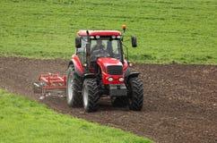 Piccola scala che coltiva con il trattore e l'aratro nel campo Fotografia Stock