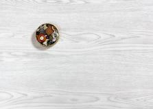 Piccola scatola del metallo in pieno di bottoni su un fondo di legno Fotografia Stock