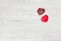 Piccola scatola in forma di cuore rossa in pieno di perni su un fondo di legno Fotografie Stock