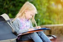 Piccola scolara adorabile che studia all'aperto il giorno luminoso di autunno Giovane studente che fa il suo compito Istruzione p Immagine Stock