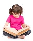 Piccola scolara che legge grande libro Isolato su priorità bassa bianca Fotografia Stock