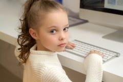 Piccola scolara che si siede con la tastiera di computer allo scrittorio in laboratorio fotografie stock