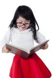Piccola scolara che studia con un manuale Immagini Stock