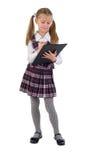 Piccola scolara con il dispositivo di piegatura nero. Fotografia Stock